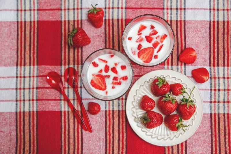 Dois vidros do iogurte, morangos frescas vermelhas estão na placa cerâmica com as colheres plásticas na toalha de mesa da verific imagem de stock royalty free