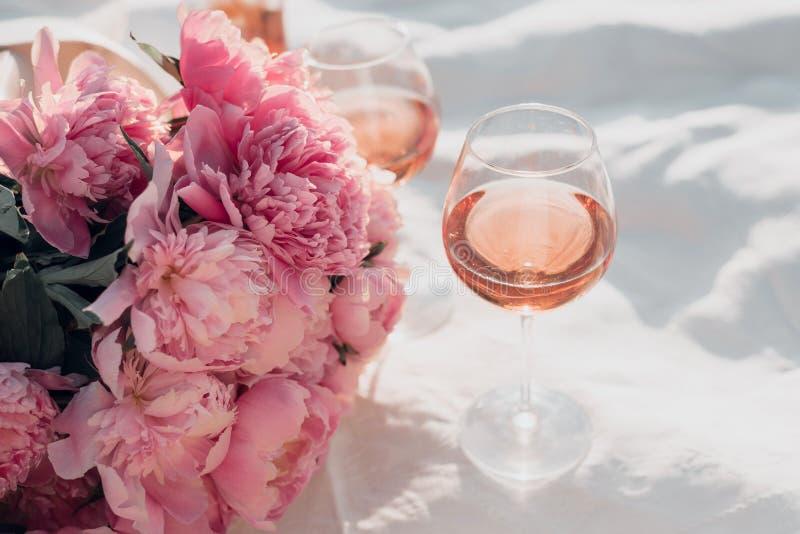 Dois vidros do ramalhete do vinho cor-de-rosa e da peônia no piquenique do por do sol fotografia de stock royalty free