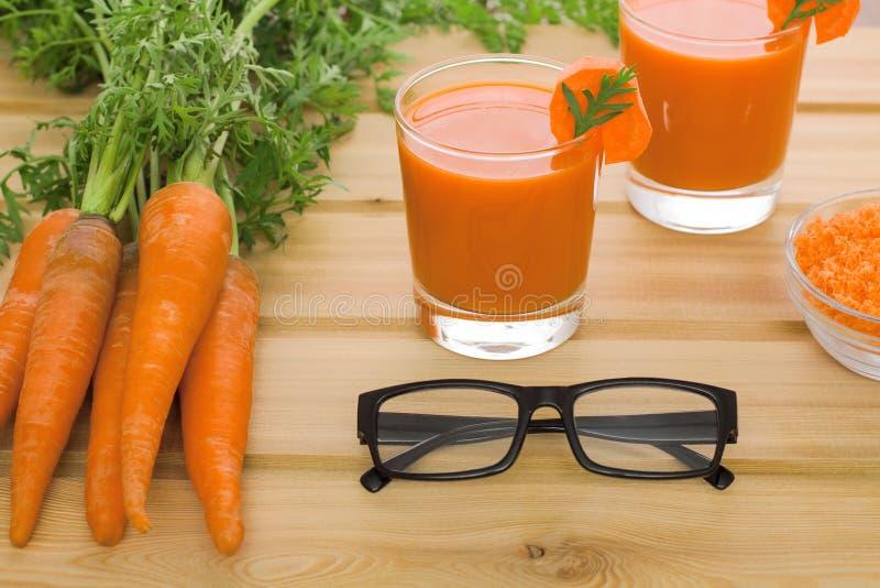 Dois vidros do suco de cenoura fresco e de espetáculos preto-orlarados fotos de stock