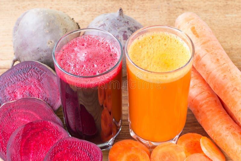 Dois vidros do suco fresco da beterraba e de cenoura, das beterrabas e das cenouras vegetais na tabela de madeira foto de stock
