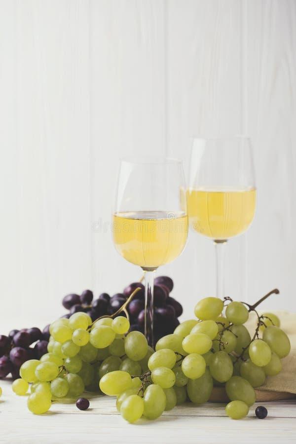 Dois vidros do vinho branco, de uvas frescas e de peras fotografia de stock royalty free