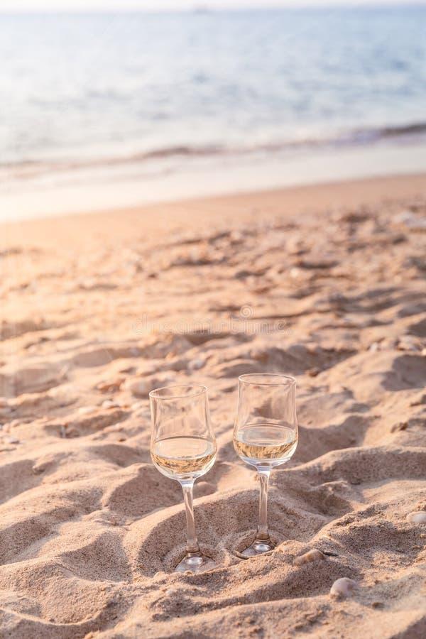 Dois vidros do vinho branco na praia no dia ensolarado do verão imagens de stock