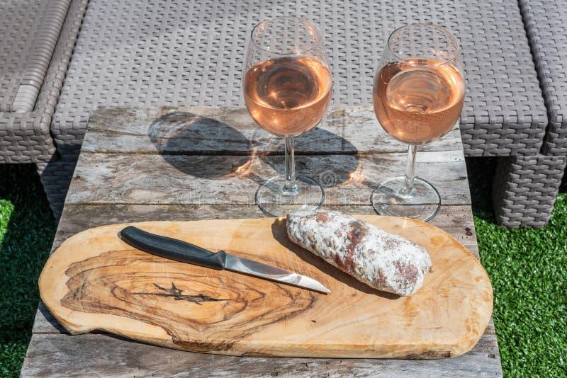 Dois vidros do vinho cor-de-rosa e de uma salsicha secada com uma faca em uma tabela de madeira foto de stock royalty free