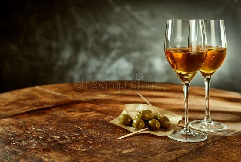 Dois vidros do vinho e das azeitonas na tabela de madeira fotografia de stock royalty free