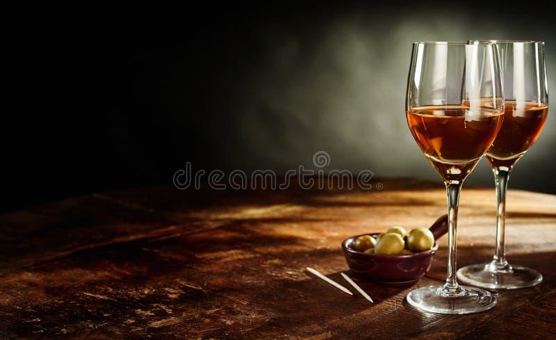 Dois vidros do vinho e das azeitonas na tabela de madeira fotos de stock royalty free