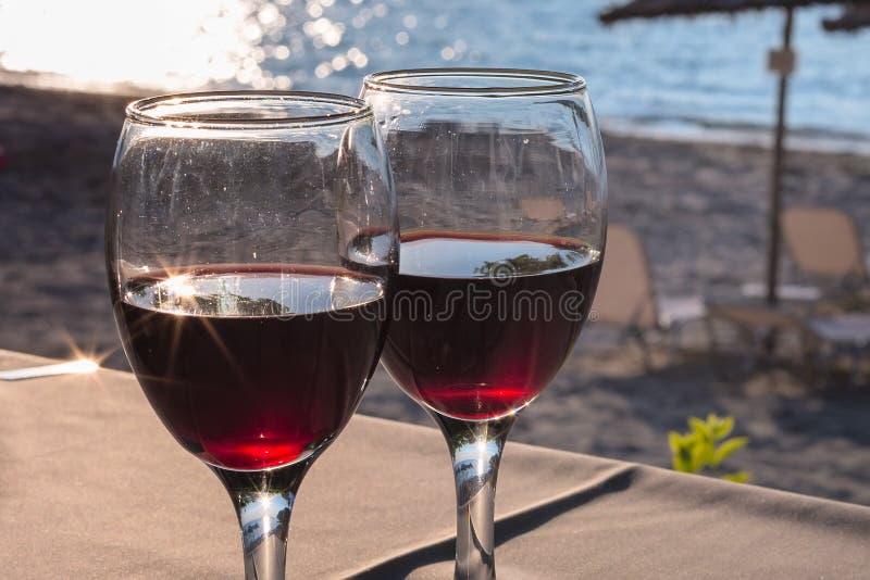 Dois vidros do vinho tinto com reflexão do sol, mar, fundo das férias de verão imagem de stock royalty free