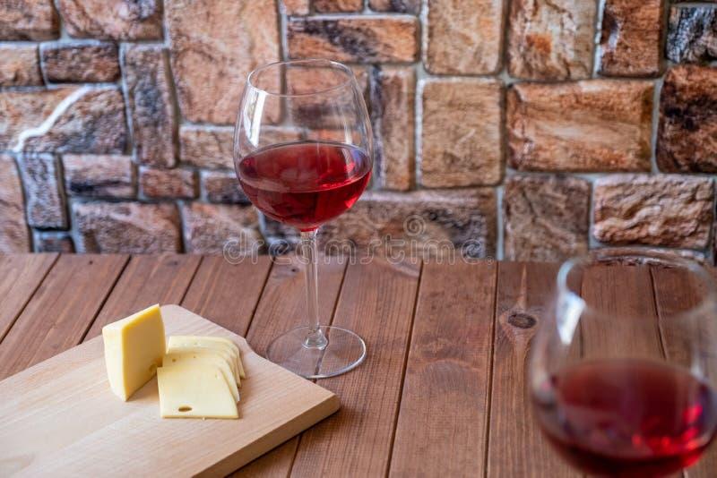 Dois vidros do vinho tinto e do queijo cortado em uma tabela de madeira foto de stock royalty free