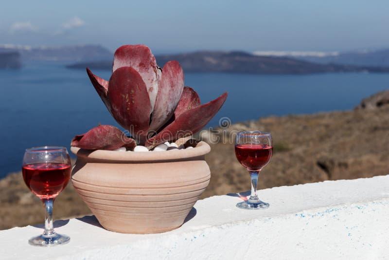 Dois vidros do vinho tinto saboroso com vista surpreendente do mar na ilha de Santorini imagem de stock