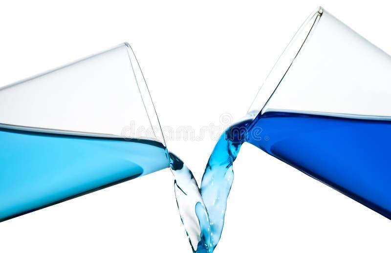 Dois vidros que derramam a água ou um liqui azul similar foto de stock royalty free