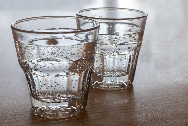 Dois vidros recentemente derramados da água gasosa isolados na madeira foto de stock