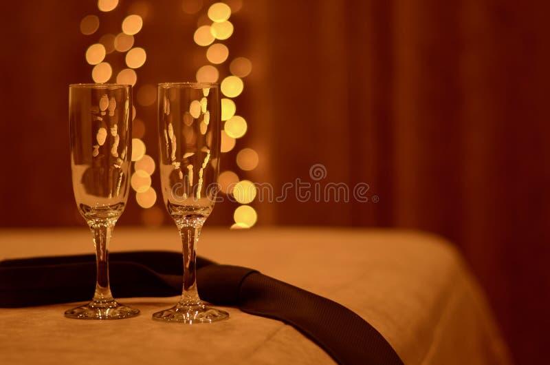 Dois vidros rom?nticos na borda da cama ? vista das luzes mornas, ao lado do la?o de um homem foto de stock royalty free