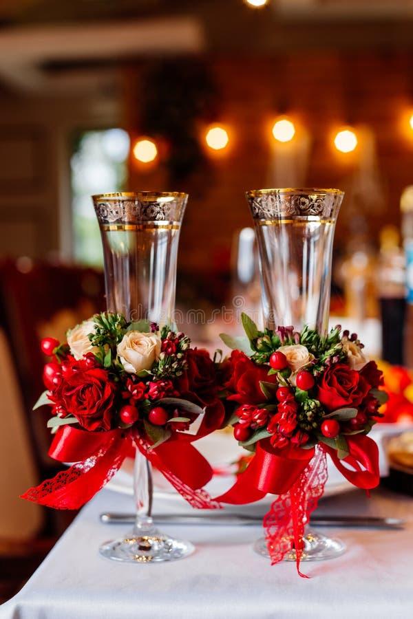 Dois vidros vazios do casamento, decorados com as hortaliças, as rosas vermelhas e a fita, estando na tabela de banquete fotos de stock royalty free