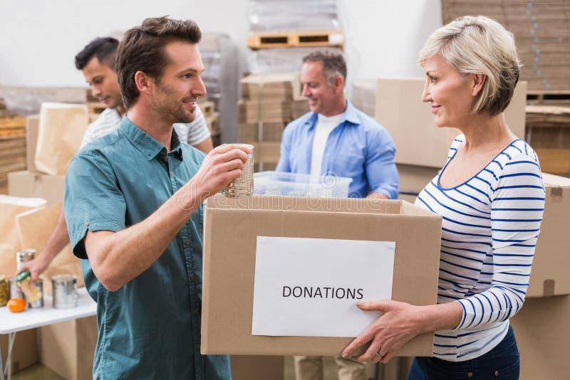 Dois voluntários que guardam uma caixa das doações fotografia de stock