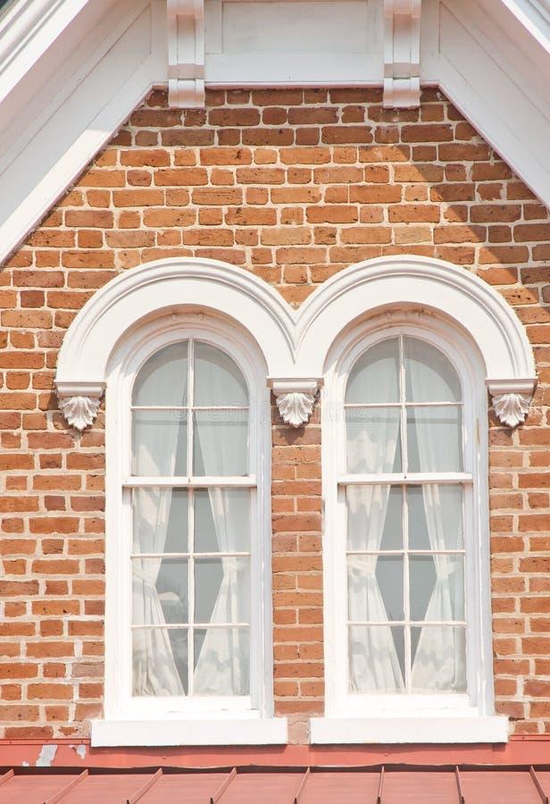 Dois Windows no Dormer do tijolo foto de stock