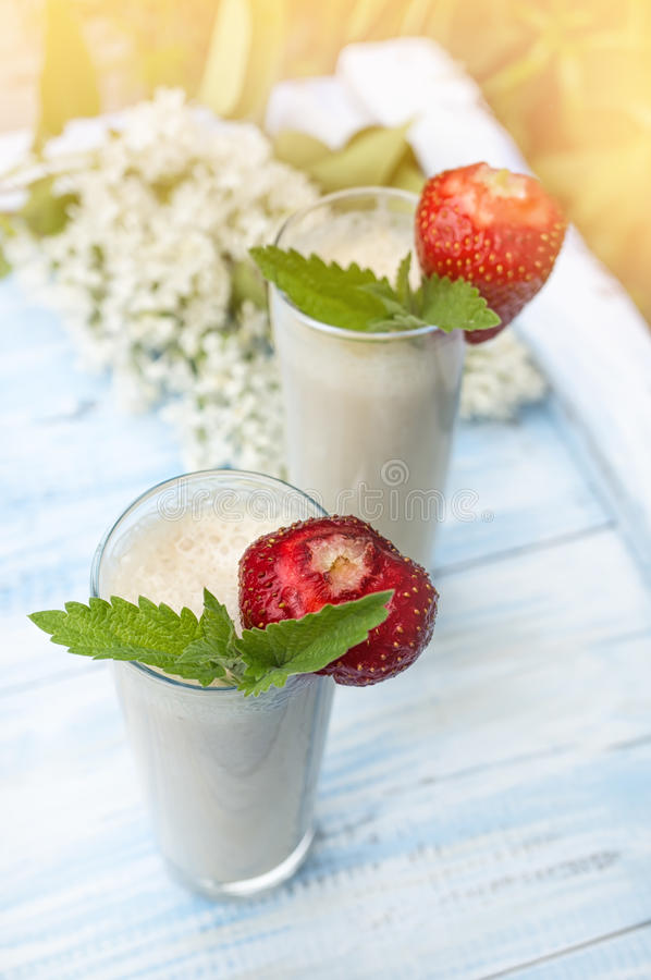 Dojny smoothie z truskawkami i bananem na tle zielone rośliny w zmierzchu w słońcu Pionowo rama obraz stock