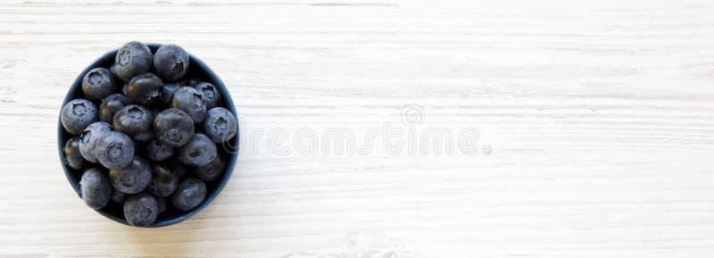 Dojrzałe czarne jagody w błękitnym pucharze nad białym drewnianym tłem, odgórny widok Lato jagoda Od above, mieszkanie, koszt sta zdjęcie royalty free