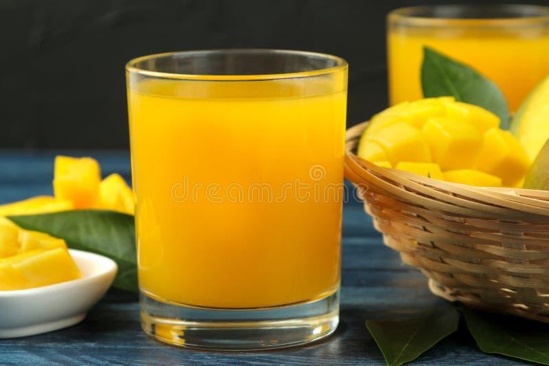 Dojrzała świeża mangowa owoc, plasterki i mangowy sok w szkle na błękitnym drewnianym stole owoce tropikalne fotografia stock