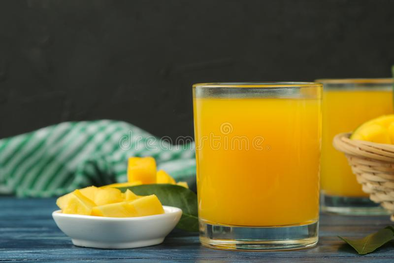 Dojrzała świeża mangowa owoc, plasterki i mangowy sok w szkle na błękitnym drewnianym stole owoce tropikalne zdjęcie stock