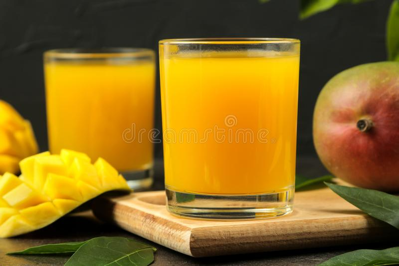 Dojrzała świeża mangowa owoc, plasterki i mangowy sok w szkle na ciemnym tle owoce tropikalne obraz stock
