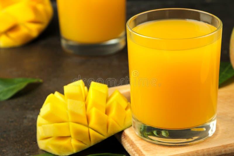 Dojrzała świeża mangowa owoc, plasterki i mangowy sok w szkle na ciemnym tle owoce tropikalne zdjęcie stock