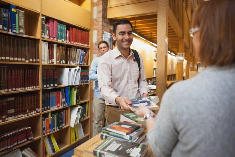 Dojrzała żeńska bibliotekarka wręcza książkę młody człowiek fotografia royalty free