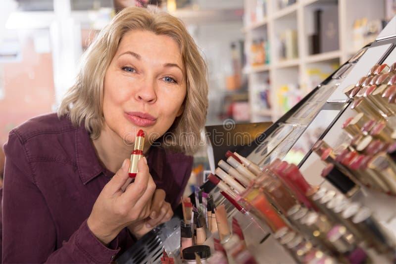 Dojrzała żeńska klienta kupienia czerwieni pomadka zdjęcie stock