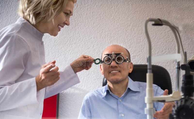 dojrzała blond kobieta i mężczyzna przechodzić na emeryturę oftalmologa czeka wzrok w klinice zdjęcie royalty free