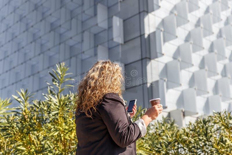 Dojrzała blondynki kobieta sprawdza jej telefon komórkowego w ulicie, podczas gdy mieć kawę fotografia royalty free
