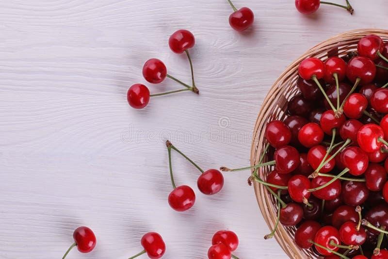 dojrzała czerwona wiśnia w koszu na białym drewnianym stole z miejscem dla inskrypci Odgórny widok zdjęcie royalty free