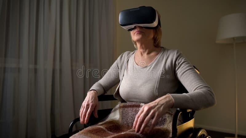 Dojrzała dama jest ubranym vr słuchawki widzieć magicznego technologicznego słowo w wózku inwalidzkim obraz royalty free