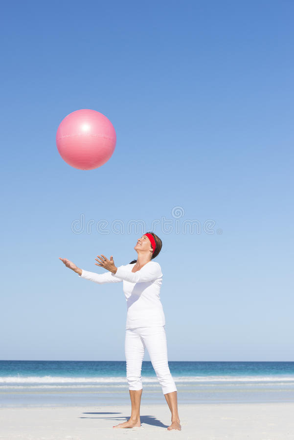 Dojrzała kobieta łapie gimnastyczną piłkę przy plażą fotografia royalty free