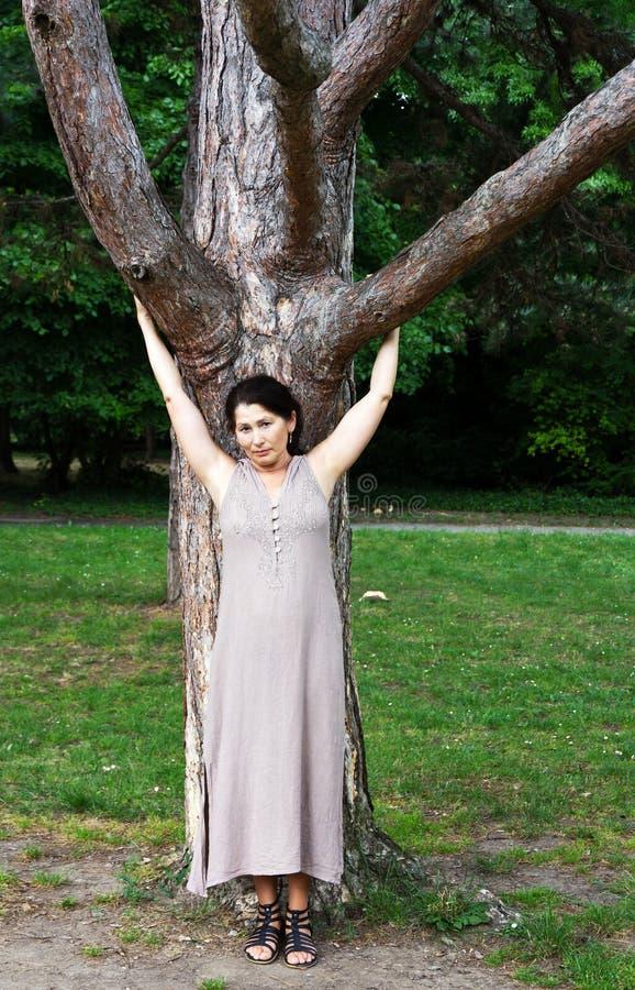 Dojrzała kobieta blisko drzewa w parku zdjęcia stock