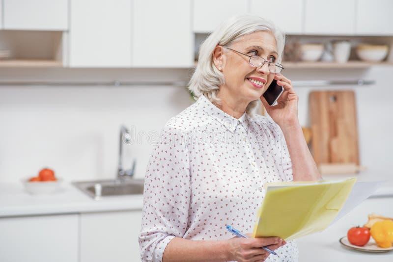 Dojrzała kobieta dzwoni użyteczności usługa w domu zdjęcia royalty free