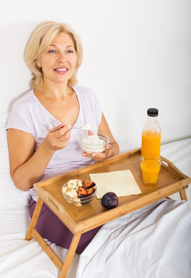 Dojrzała kobieta Ma śniadanie w łóżku zdjęcia stock