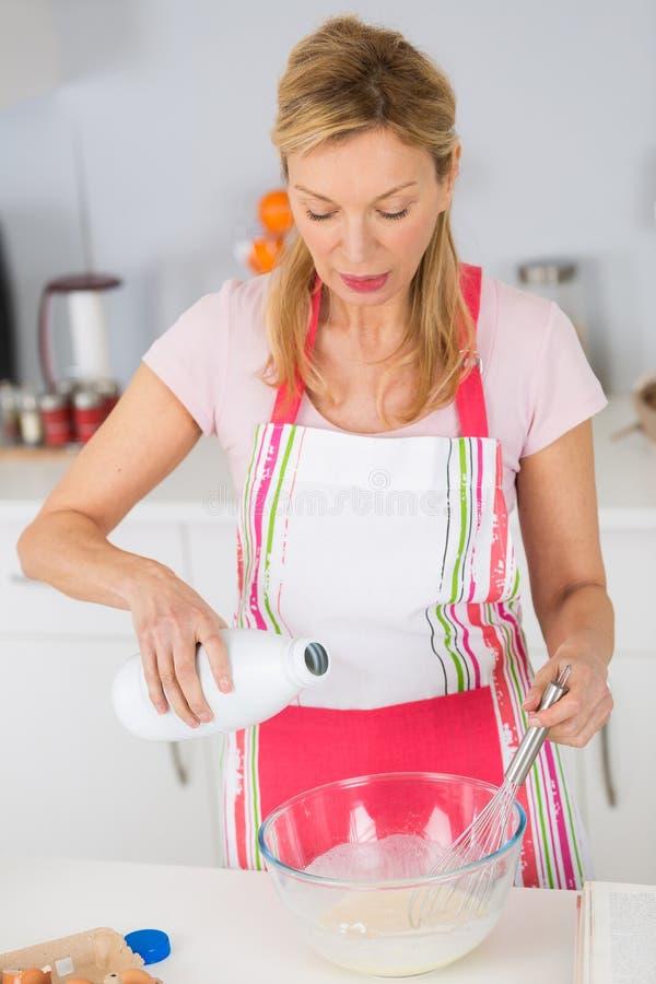 Dojrzała kobieta miesza składniki dla wyśmienicie smakowitego torta lub tarta obraz royalty free