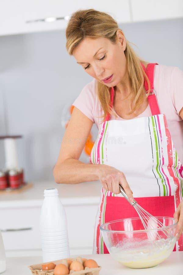 Dojrzała kobieta miesza składniki dla wyśmienicie smakowitego torta lub tarta obraz stock