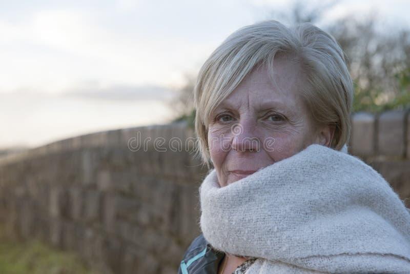 Dojrzała kobieta outdoors w zimie jest ubranym szalika fotografia royalty free