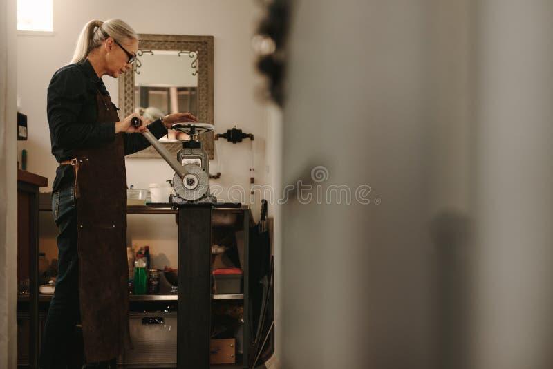 Dojrzała kobieta pracuje w złotnika warsztacie zdjęcie stock