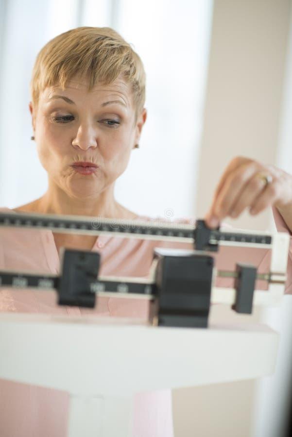 Dojrzała kobieta Przystosowywa Ślizgową ciężar skala zdjęcie royalty free