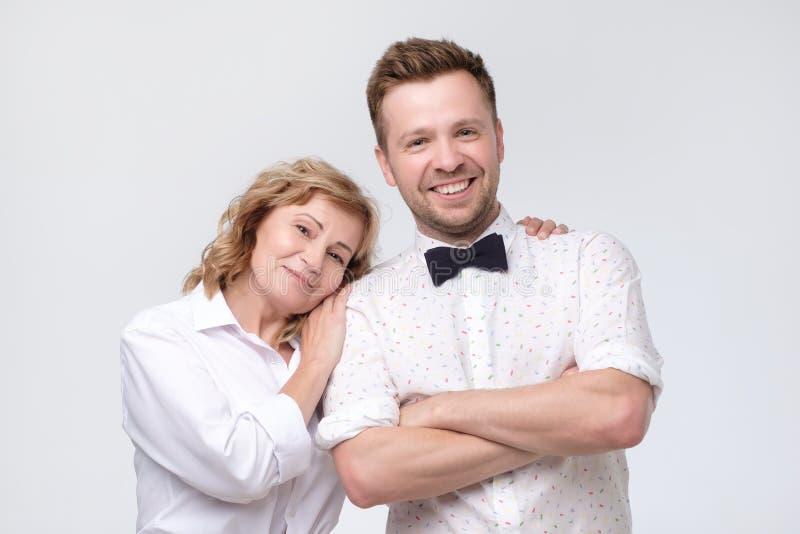 DojrzaÅ'a kobieta przytulajÄ…ca swojego przystojnego syna zdjęcia stock