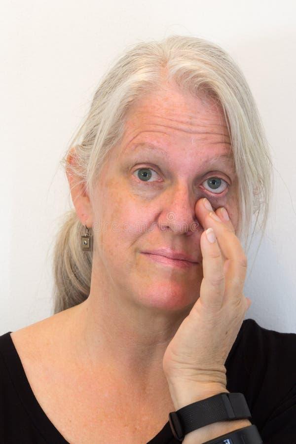 Dojrzała kobieta, ręki ciągnięcia puszka powieka, patrzeje naprzód, naturalna żadny makeup, neutralny tło zdjęcia stock