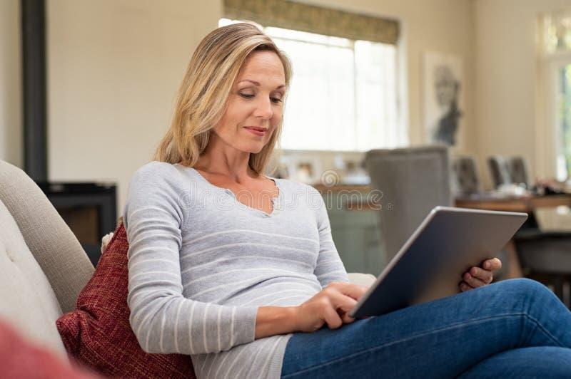 Dojrzała kobieta relaksuje z cyfrową pastylką obraz royalty free