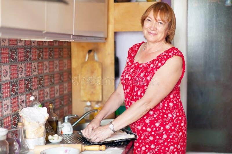 Dojrzała kobieta robi kulebiakowi z plombowaniami obrazy royalty free