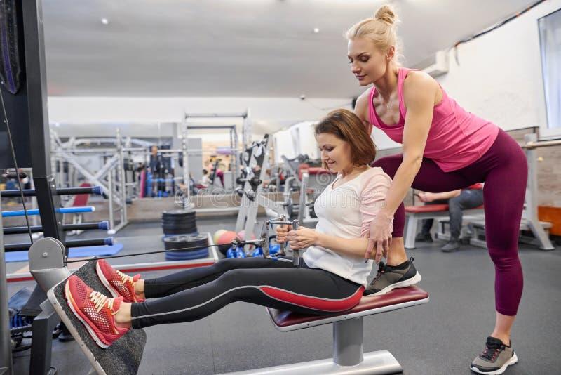 Dojrzała kobieta robi sportowi ćwiczy z osobistym trenerem przy gym Żeński instruktor pomaga starej kobiety zdjęcie royalty free