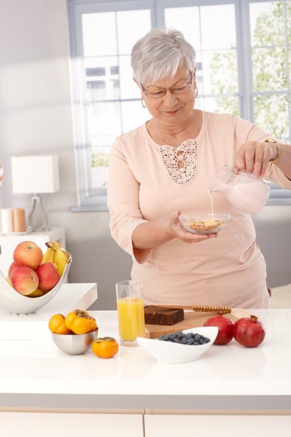 Dojrzała kobieta robi zdrowemu śniadaniu obraz royalty free