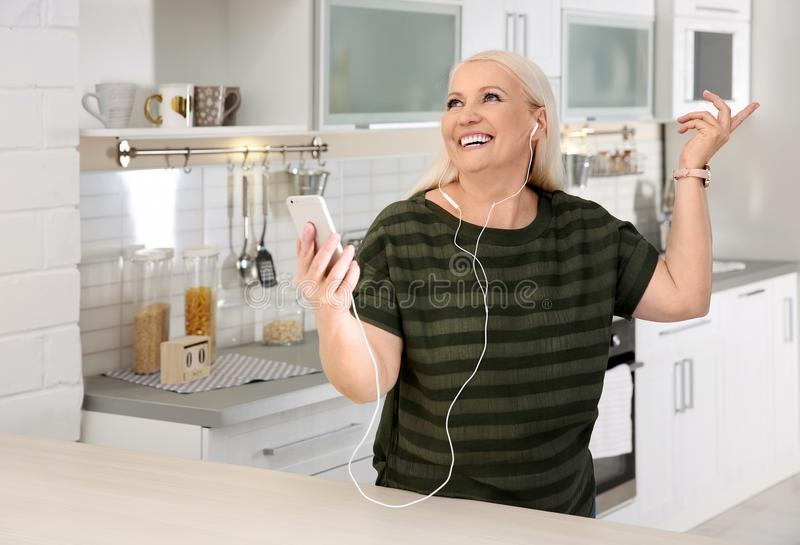 Dojrzała kobieta słucha muzyka na telefonie komórkowym zdjęcia royalty free