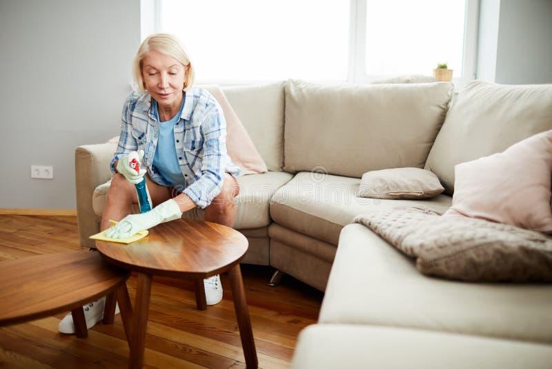Dojrzała kobieta usuwa pył od stolika do kawy zdjęcia stock