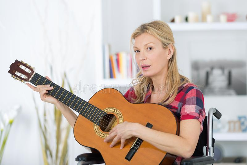 Dojrzała kobieta w wózku inwalidzkim bawić się gitarę zdjęcie stock