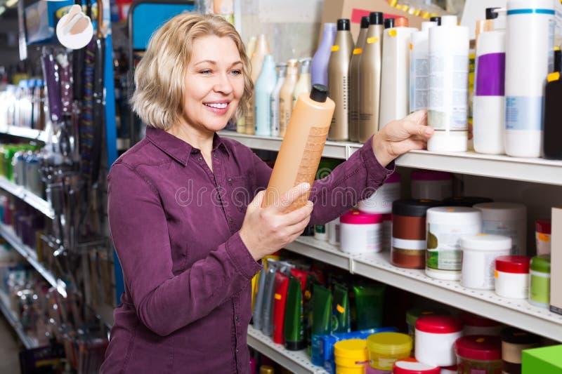 Dojrzała kobieta wybiera szampon w sklepie zdjęcia royalty free