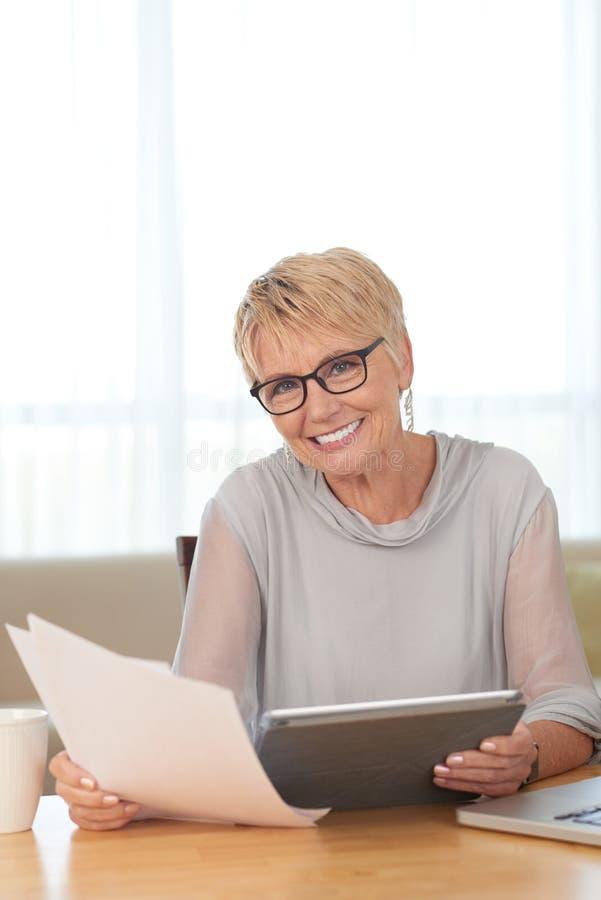 Dojrza?a kobieta z pastylka komputerem osobistym w domu obraz royalty free
